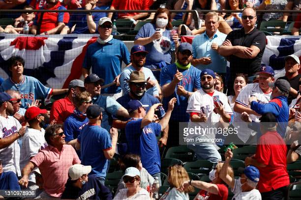 Fans scramble for a foul ball in the second inning as the Texas Rangers take on the Toronto Blue Jays on Opening Day at Globe Life Field on April 05,...