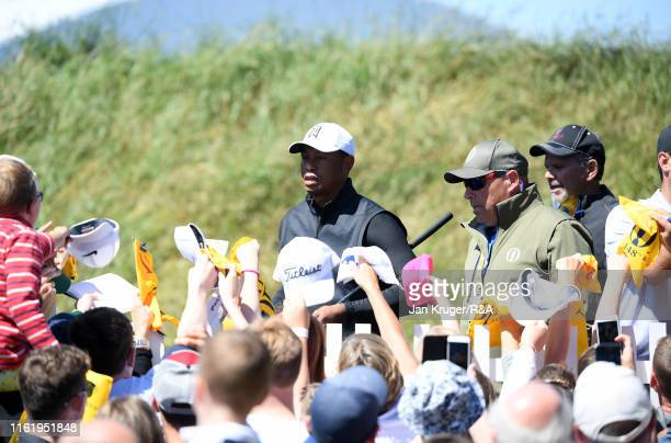 Fans seek autographs from Tiger Woods of the United States during a practice round prior to the 148th Open Championship held on the Dunluce Links at...