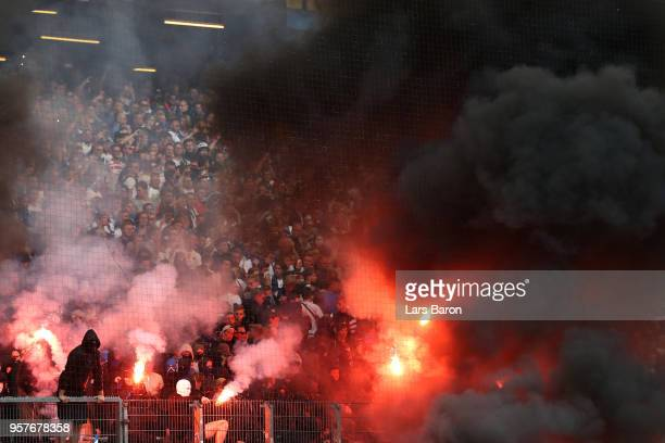 Fans set off flares during the Bundesliga match between Hamburger SV and Borussia Moenchengladbach at Volksparkstadion on May 12 2018 in Hamburg...