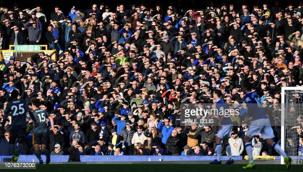 Fans sheild their eyes from the sun as they watch the play during the English Premier League football match between Everton and Leicester City at...
