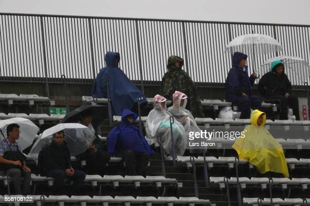 Fans shelter from the rain during practice for the Formula One Grand Prix of Japan at Suzuka Circuit on October 6 2017 in Suzuka