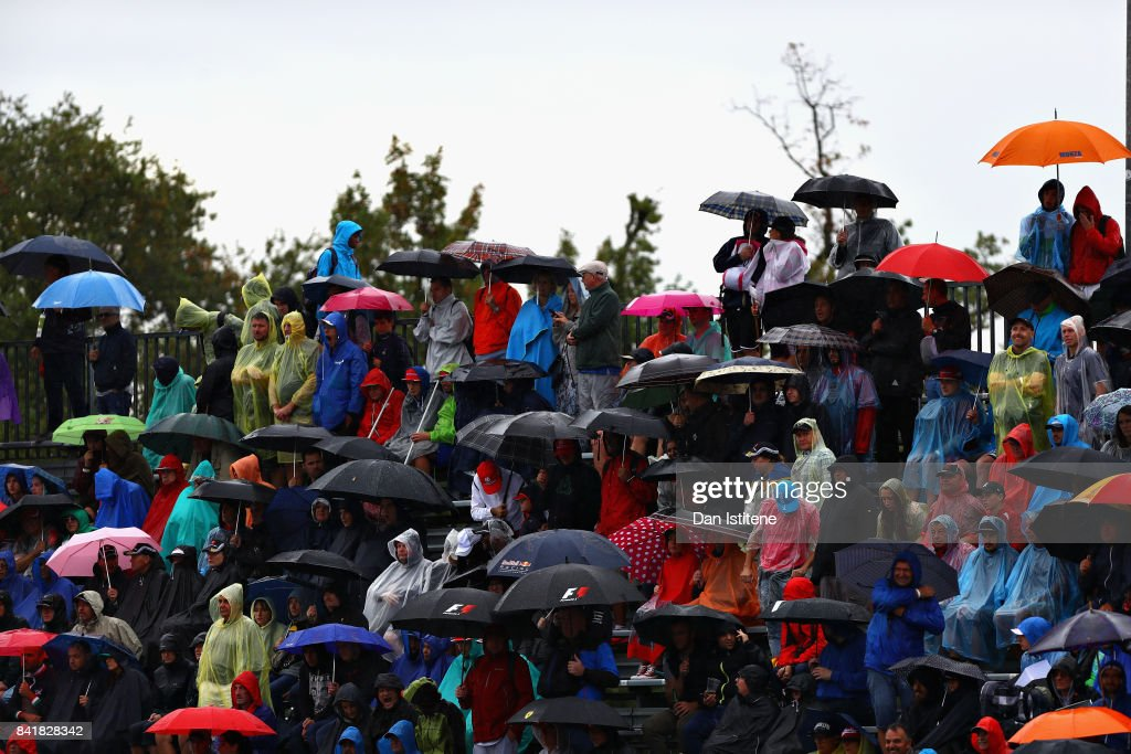 Fans shelter from the rain during qualifying for the Formula One Grand Prix of Italy at Autodromo di Monza on September 2, 2017 in Monza, Italy.