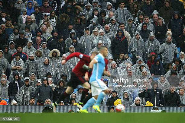 Fans shelter from the rain in ponchos during the Barclays Premier League match between Manchester City and West Bromwich Albion at Etihad Stadium on...