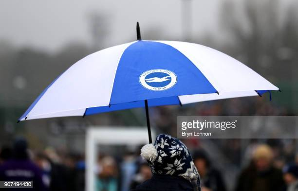 Fans shelter from the rain prior to the Premier League match between Brighton and Hove Albion and Chelsea at Amex Stadium on January 20 2018 in...