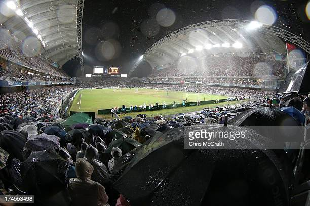 Fans shelter under umbrellas amongst heavy rain during the Barclays Asia Trophy Final match between Manchester City and Sunderland at Hong Kong...