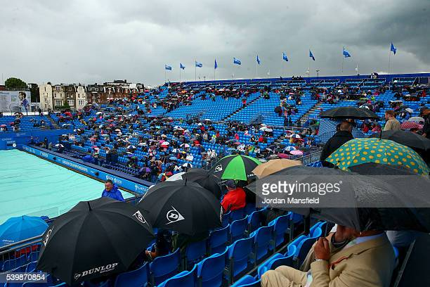 Fans shelter under umbrellas as rain delays play during day one of the Aegon Championships at the Queens Club on June 13 2016 in London England