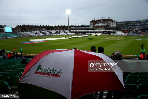 Fans shelter under umbrellas as rain delays play during the ICC Champions Trophy match between Australia and Bangladesh at The Kia Oval on June 5...