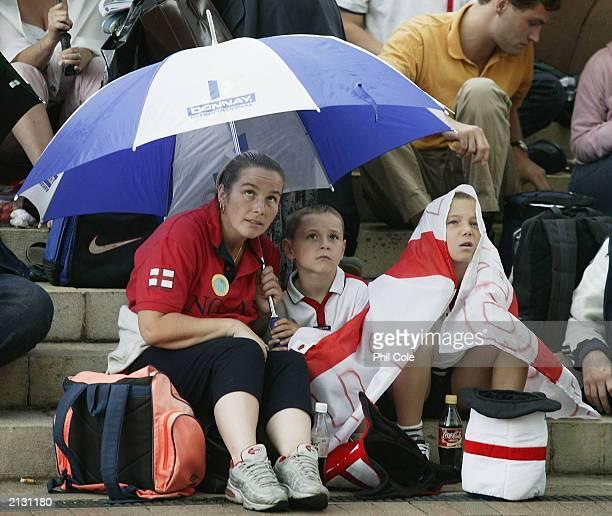 Fans shelter under umbrellas as rain stops play during the Tim Henman of Great Britain against Sebastien Grosjean of France during the men's quarter...