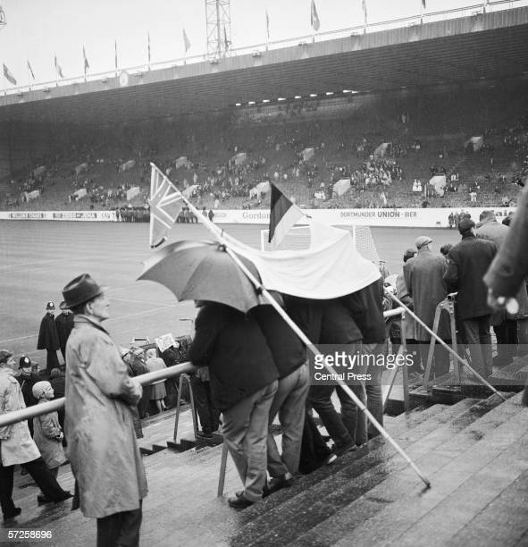 Fans sheltering from the rain under a German and British flag at Hillsborough Stadium in Sheffield before Switzerland play Spain during the Group B...