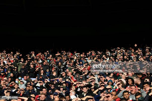 Fans shield their eyes from the bright sunshine during the Premier League match between Leicester City and Manchester United at The King Power...
