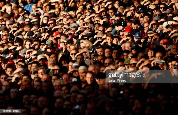 Fans shield their eyes from the sun during the Premier League match between Arsenal FC and Everton FC at Emirates Stadium on September 23 2018 in...