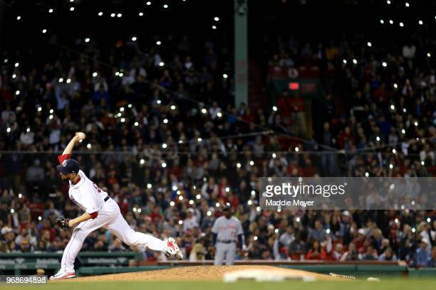 Fans shine the lights on their cell phones in the stands as Matt Barnes of the Boston Red Sox pitches against the Detroit Tigers during the seventh...