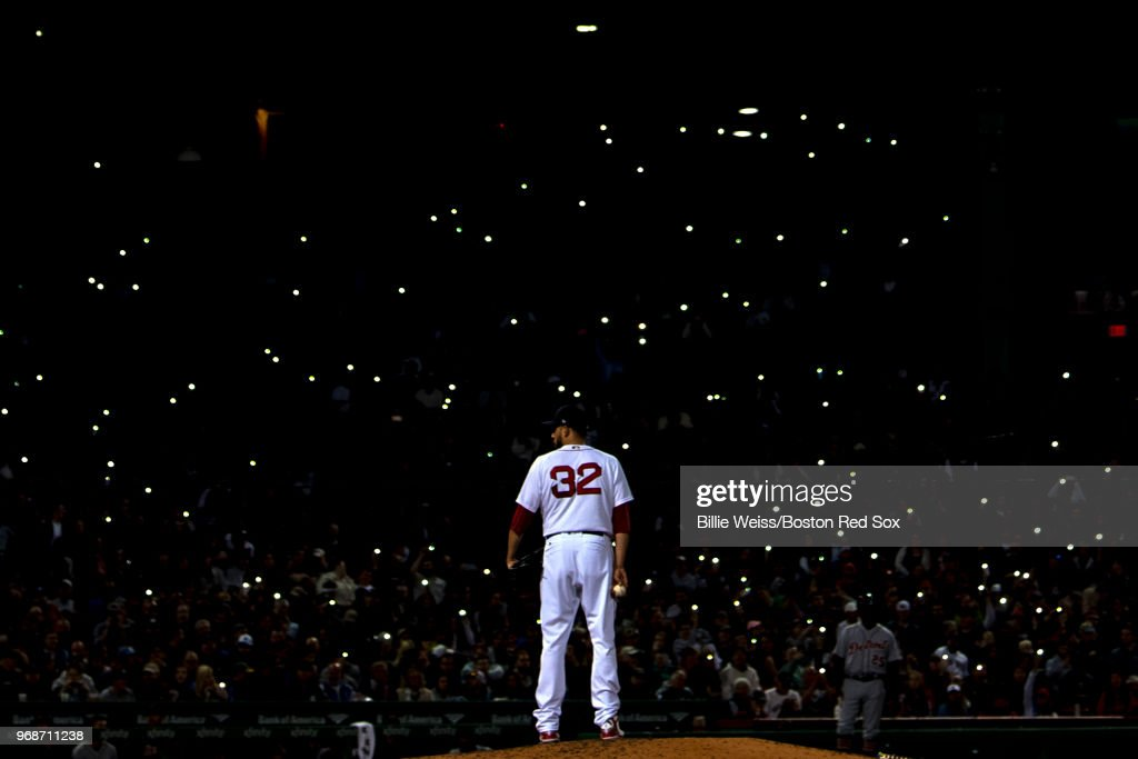 Fans shine the lights on their cell phones in the stands as Matt Barnes #32 of the Boston Red Sox looks on during the seventh inning of a game against the Detroit Tigers on June 6, 2018 at Fenway Park in Boston, Massachusetts.