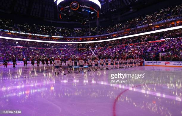 Fans shine their phone lights as Buffalo Sabres and Montreal Canadiens players stand in recognition of Hockey Fights Cancer prior to an NHL game on...