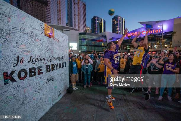 Fans shoot baskets at a memorial wall near Staples Center in honor of former NBA great Kobe Bryant who along with his 13yearold daughter Gianna died...