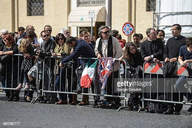 Fans show English and Italian flags as they wait in Saint Peter's Square the arrival of Queen Elizabeth II on April 3 2014 in Rome Italy During their...