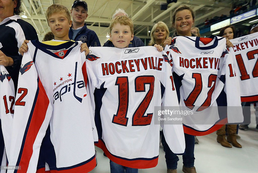 Fans show off the signed jerseys they were given by members of the Washington Capitals after facing the Winnipeg Jets during Kraft Hockeyville Day 2 at Yardmen Arena on September 14, 2013 in Belleville, Ontario, Canada.