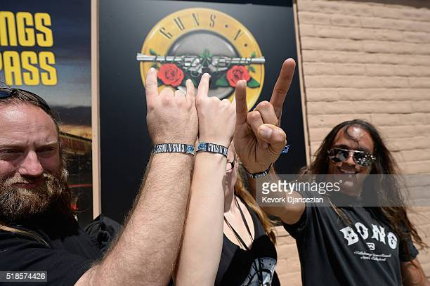 Fans show off their wristbands after waiting in line as Guns N' Roses announce concert and ticket giveaway at Tower Records on April 1, 2016 in West...