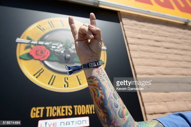 A fans shows off their wristband after waiting in line as Guns N' Roses announce concert and ticket giveaway at Tower Records on April 1 2016 in West...