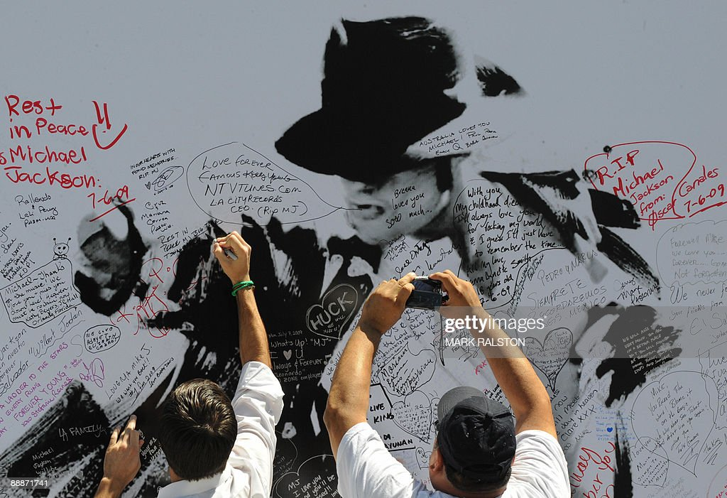Fans sign a Michael Jackson poster covered in messages outside the Staples Center, which will be the site of a memorial service for musical legend after his recent death, in Los Angeles on July 6, 2009. A total of 1.6 million people scrambled for tickets to Jackson's memorial service, officials said as the probe into the singer's death zeroed in on the role of drugs. The vast majority of applicants will be disappointed as only 11,000 tickets are available for Tuesday's service, along with another 6,500 to watch a live video feed at a neighboring venue. AFP PHOTO/Mark RALSTON