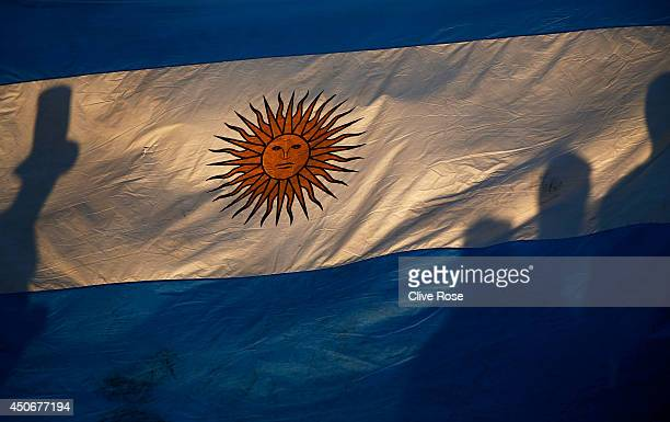 Fans silhouettes are seen through an Argentina flag prior to the 2014 FIFA World Cup Brazil Group F match between Argentina and BosniaHerzegovina at...