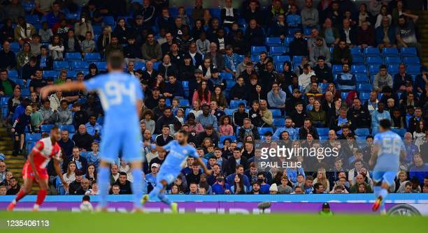 Fans sit amongst empty seats during the English League Cup third round football match between Manchester City and Wycombe Wanderers at the Etihad...