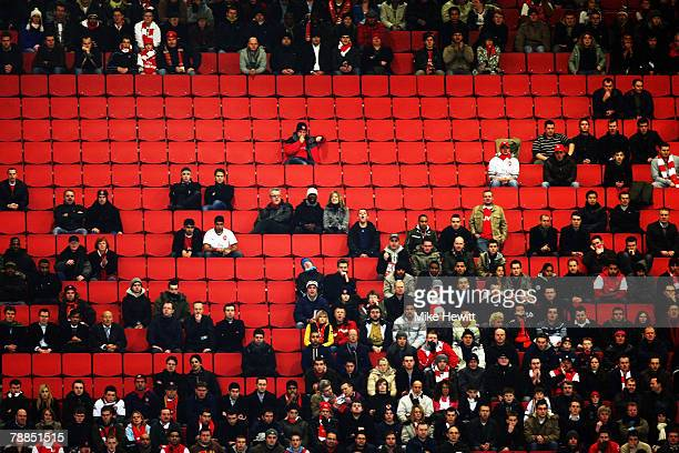 Fans sit amongst some empty seats during the Carling Cup Semi Final 1st leg match between Arsenal and Tottenham Hotspur at the Emirates Stadium on...