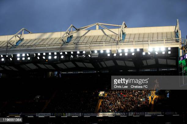 Fans sit in a patch of sun during the Premier League match between Chelsea FC and Southampton FC at Stamford Bridge on December 26 2019 in London...