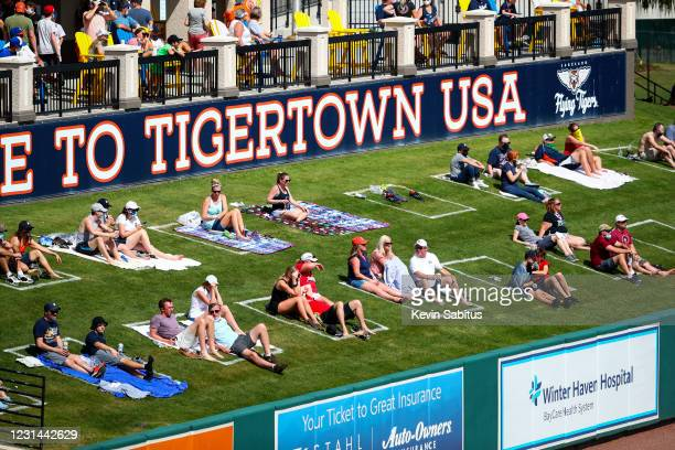 Fans sit in socially distant squares painted in center field during a spring training game between the Philadelphia Phillies and the Detroit Tigers...