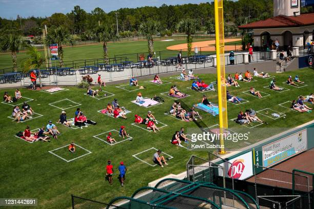 Fans sit in socially distant squares painted in left field during a spring training game between the Philadelphia Phillies and the Detroit Tigers on...