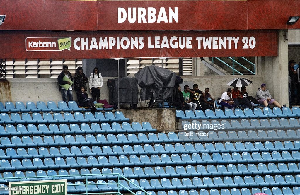 Fans sit in the rain during the CLT20 match between Auckland Aces and Delhi Daredevils from Sahara Stadium Kingsmead on October 19, 2012 in Durban, South Africa.