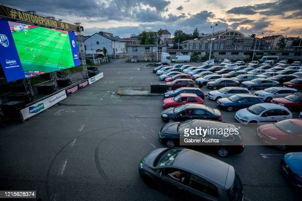 Fans sit in their cars as they watch the Czech first division football match between FC Viktoria Plzen and AC Sparta Praha at a drivein movie theater...