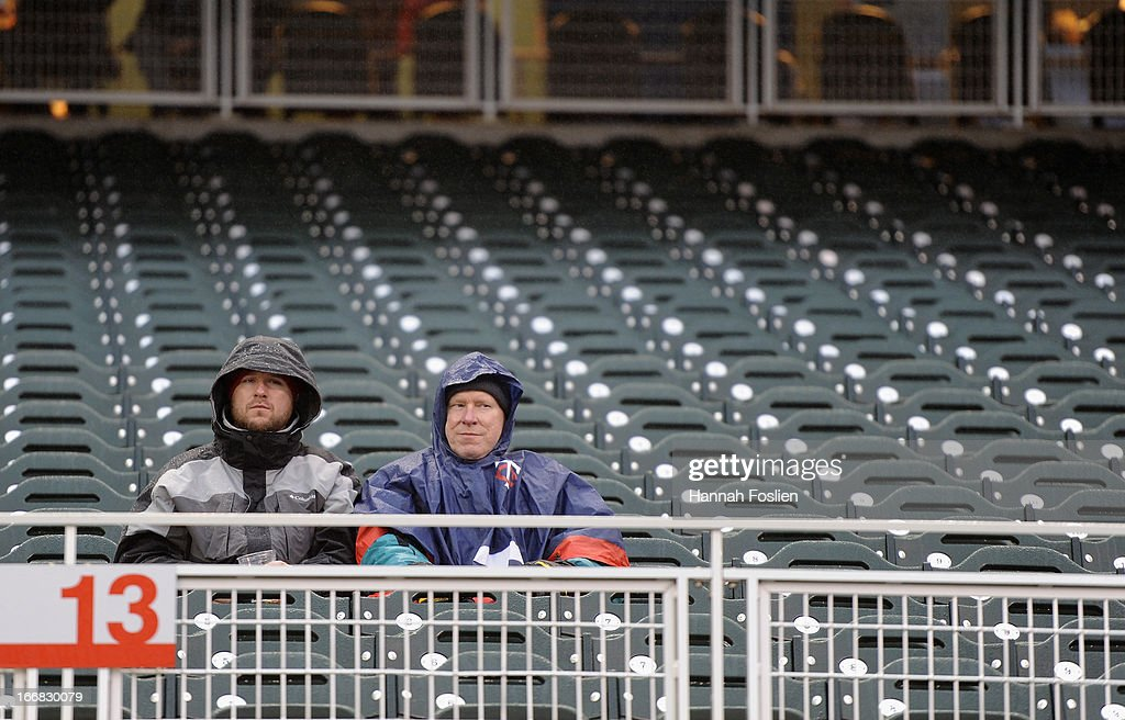 Fans sit in their sits as it rains before the game between the Minnesota Twins and the Los Angeles Angels of Anaheim on April 17, 2013 at Target Field in Minneapolis, Minnesota. The game was postponed to a later date due to cold and rain.