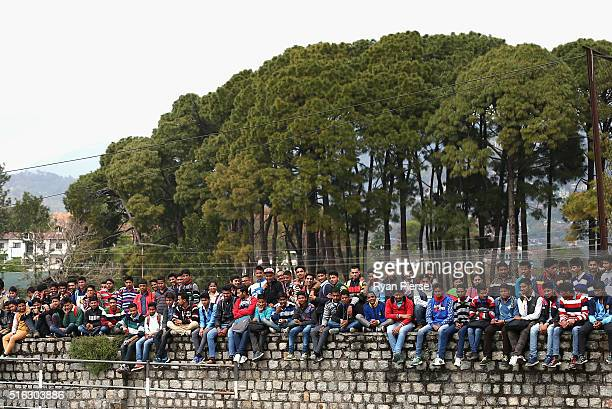 Fans sit on a wall to see over the fence during the ICC World Twenty20 India 2016 Super 10s Group 2 match between Australia and New Zealand at HPCA...