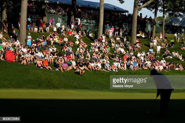 Fans sit on the 18th green during the third round of the Travelers Championship at TPC River Highlands on June 24 2017 in Cromwell Connecticut