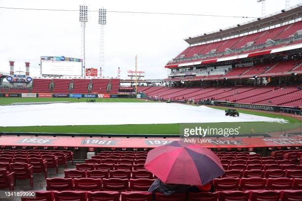 Fans sit thru the rain falling before the Cincinnati Reds game against the Pittsburgh Pirates was postponed at Great American Ball Park on September...