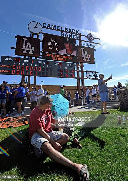 Fans sit under the center field score board during a spring training game of the Los Angeles Dodgers home opener against Chicago White Sox at...