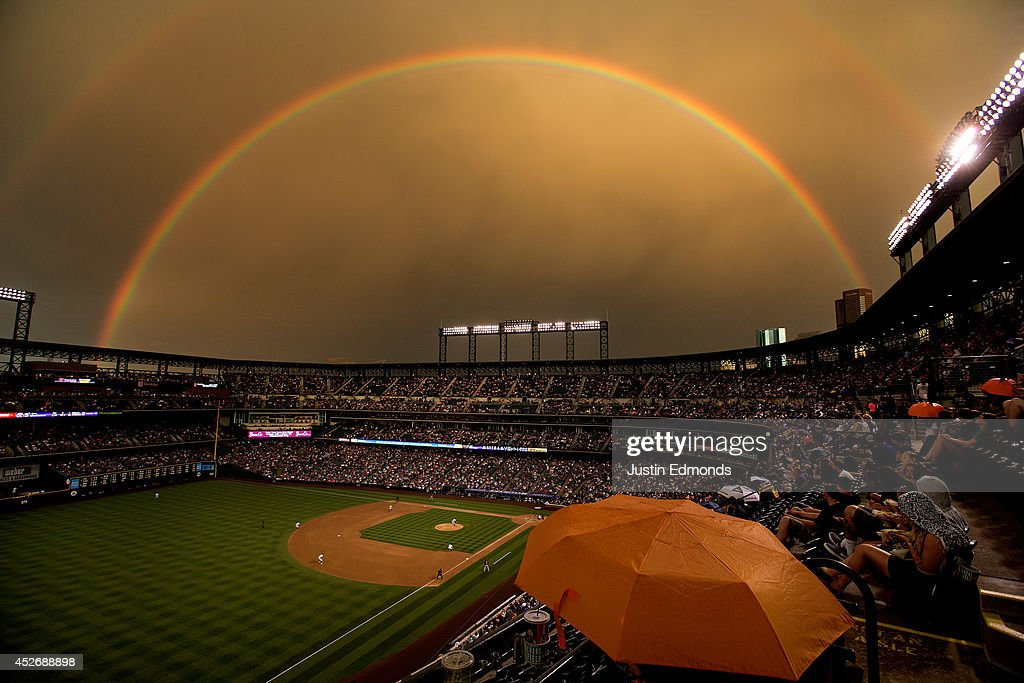 Fans sit under the cover of an umbrella as a rainbow illuminates the field while starting pitcher Brett Anderson #30 of the Colorado Rockies delivers to home plate during the fifth inning against the Pittsburgh Pirates at Coors Field on July 25, 2014 in Denver, Colorado.