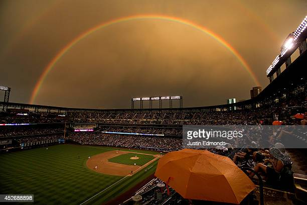 Fans sit under the cover of an umbrella as a rainbow illuminates the field while starting pitcher Brett Anderson of the Colorado Rockies delivers to...