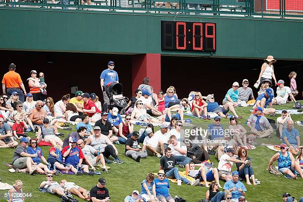 Fans sit underneath the pace of play clock in center field during the spring training game between the Chicago Cubs and the Kansas City Royals at...
