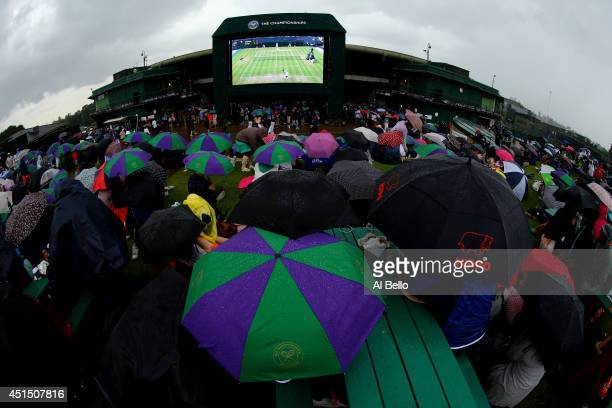 Fans sitting on Murray mound shelter under umbrellas as they watch the Andy Murray against Kevin Anderson game on the big screen on day seven of the...