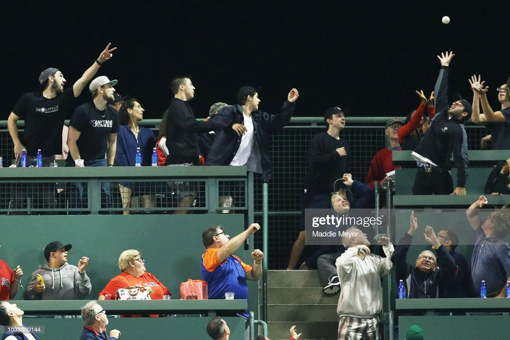 Fans sitting on the Green Monster reach for a home run hit by Amed Rosario #1 of the New York Mets during the eighth inning in the game against the Boston Red Sox at Fenway Park on September 14, 2018 in Boston, Massachusetts.
