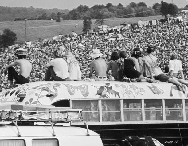 Fans sitting on top of a painted bus at the Woodstock...