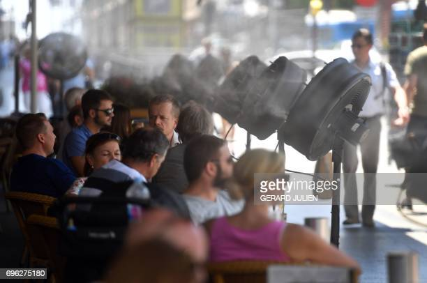 Fans spray water on clients on the terrace of the bar of the Circulo de Bellas Artes building during a heatwave in Madrid on June 15 2017 / AFP PHOTO...