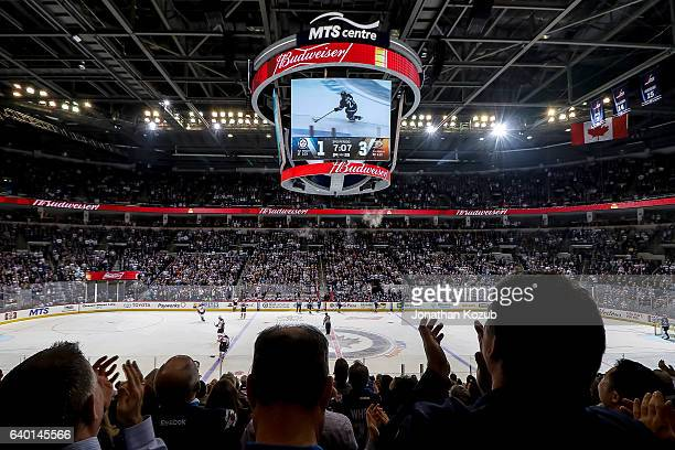 Fans stand and cheer as a third period goal scored by Nikolaj Ehlers of the Winnipeg Jets against the Anaheim Ducks is replayed on the Jumbotron at...