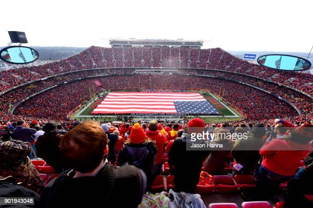 Fans stand at attention for the national anthem overlooking a 100 yard American flag prior the AFC Wild Card Playoff Game between the Kansas City...