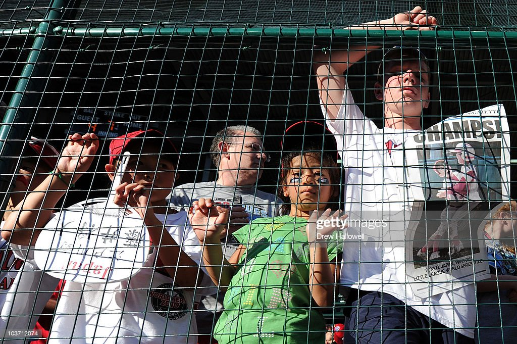 Fans stand at the fence and watch Japan celebrate after their 4-1 victory over the United States to win the Little League World Series Championship on August 29, 2010 in South Willamsport, Pennsylvania.