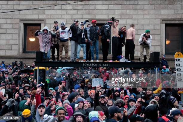 Fans stand atop a shelter in Copely Square during the Patriots Victory Parade through the streets of Boston on February 7 in Boston Massachsetts to...
