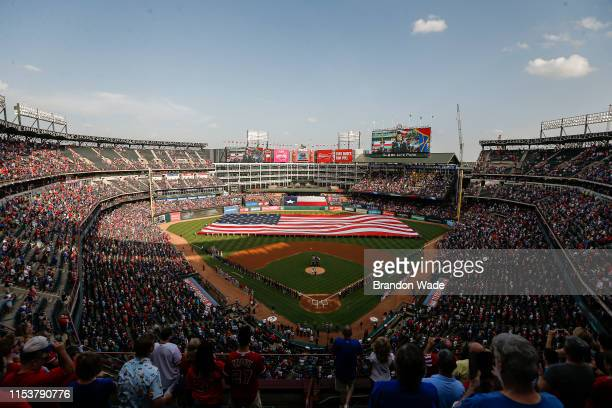 Fans stand for the playing of the National Anthem before a baseball game between the Los Angeles Angels of Anaheim and Texas Rangers at Globe Life...