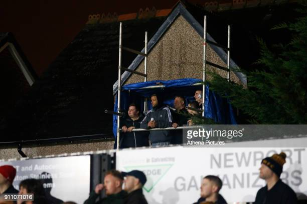 Fans stand in their own temporary stand made out of scaffolding as they watch the game over the fence during the Fly Emirates FA Cup Fourth Round...